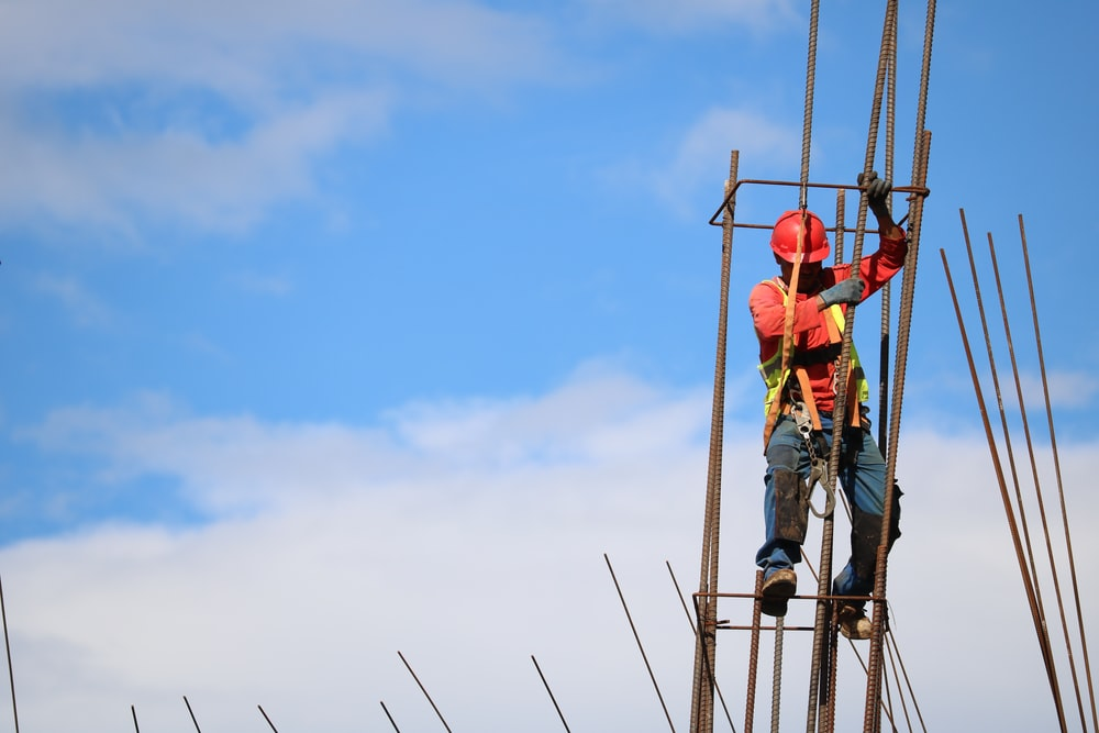 man wearing red hard hat hanged on brown rebar bar