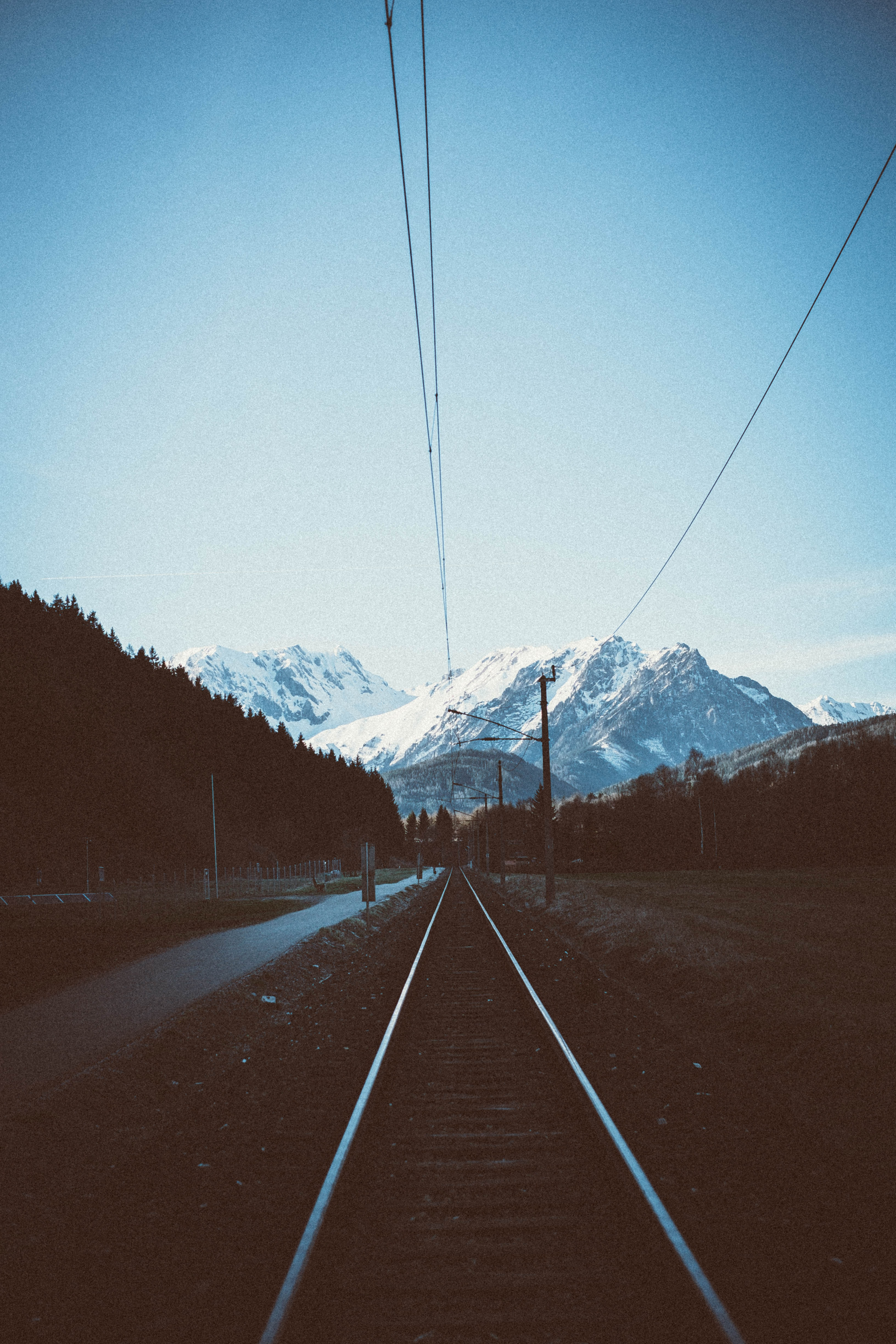 train tracks near road with snow capped mountains background