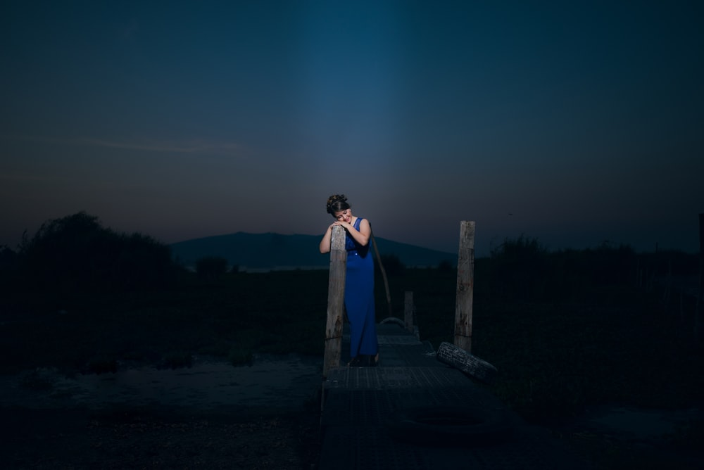 woman stands on wooden dock during night