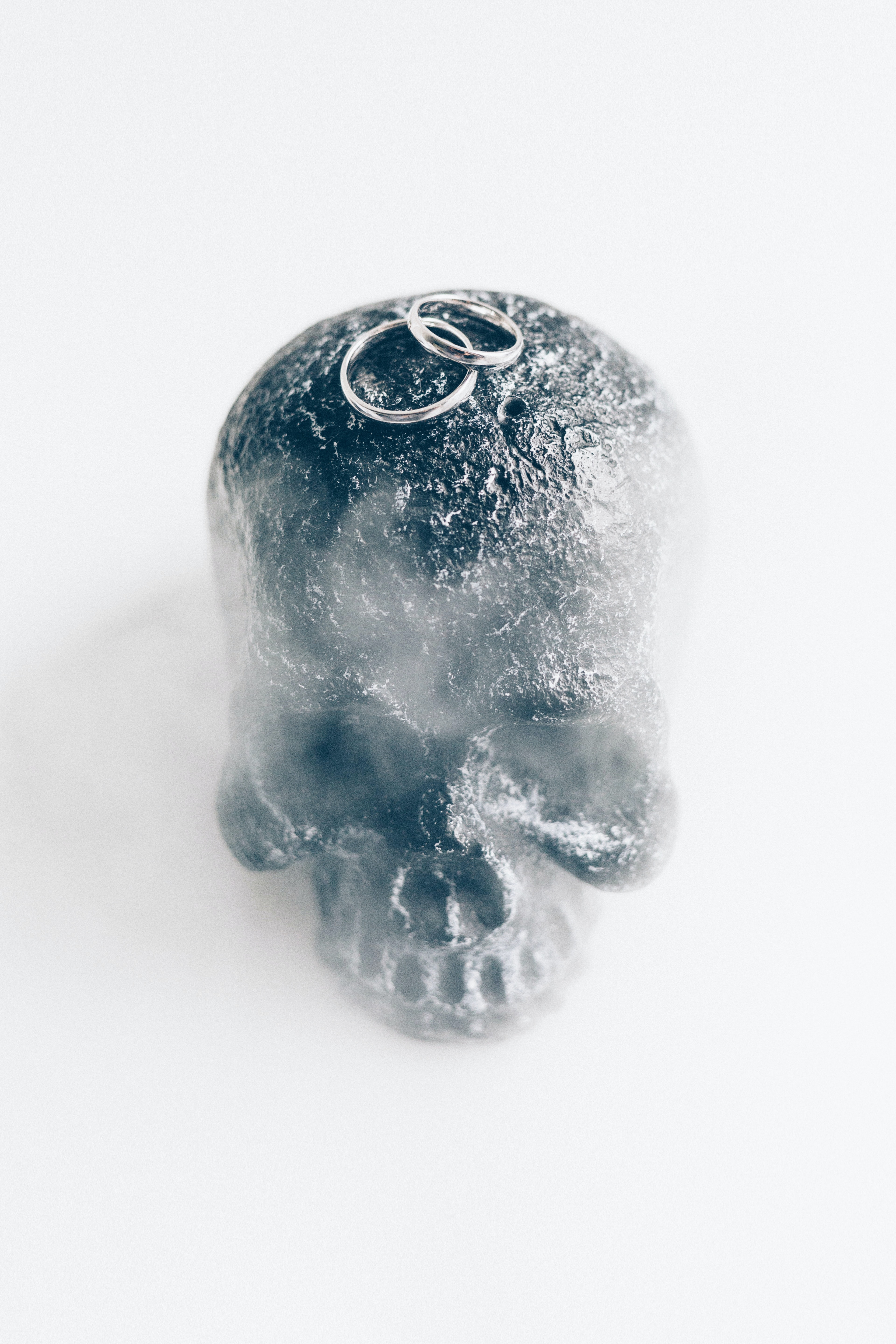 two silver-colored wedding rings on gray skull
