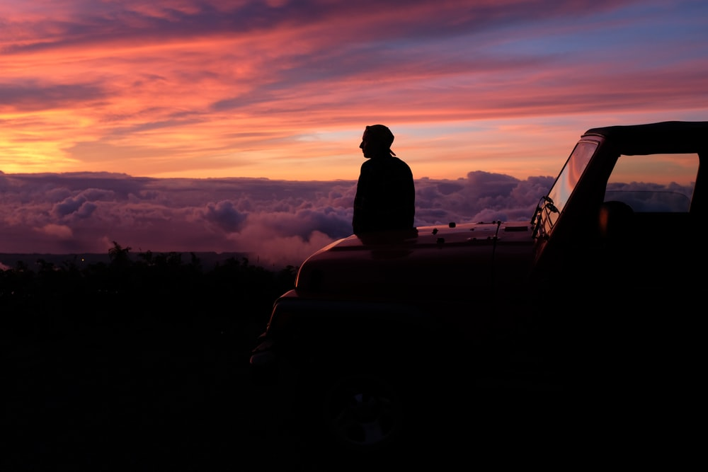 man sitting on car hood watching the skies under golden hour