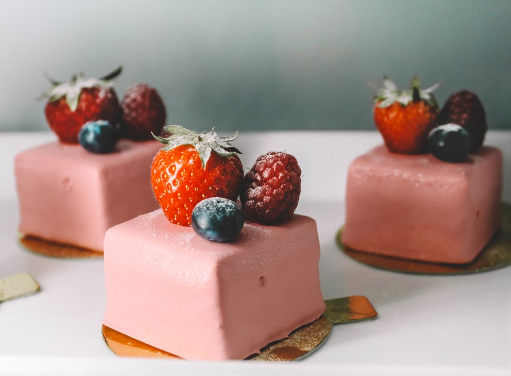 three square pastry with strawberries on top platter