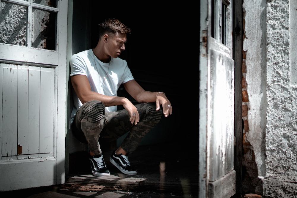 man in white crew-neck T-shirt sitting beside white door