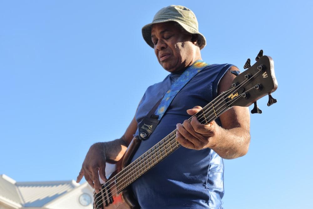 man playing electric bass guitar