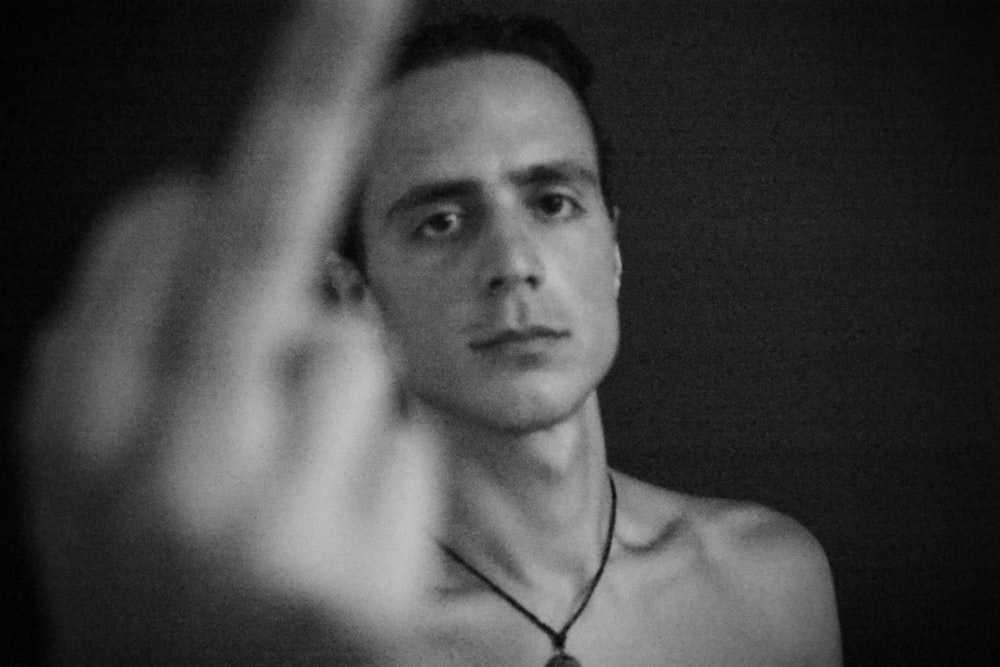 grayscale photography of man showing right hand mid finger