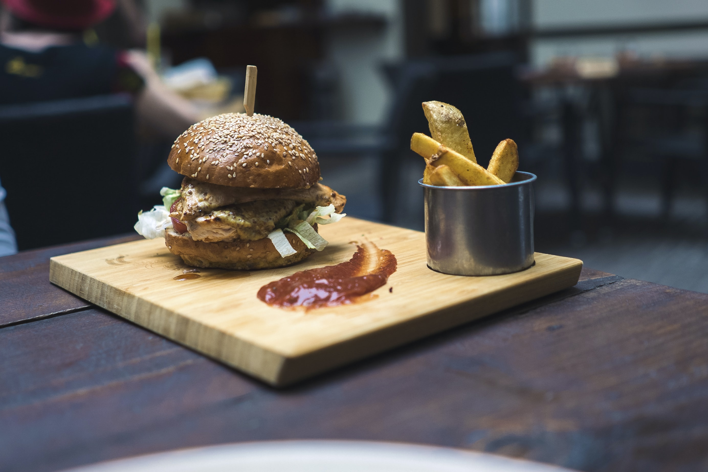 burger and fries on brown wooden tray