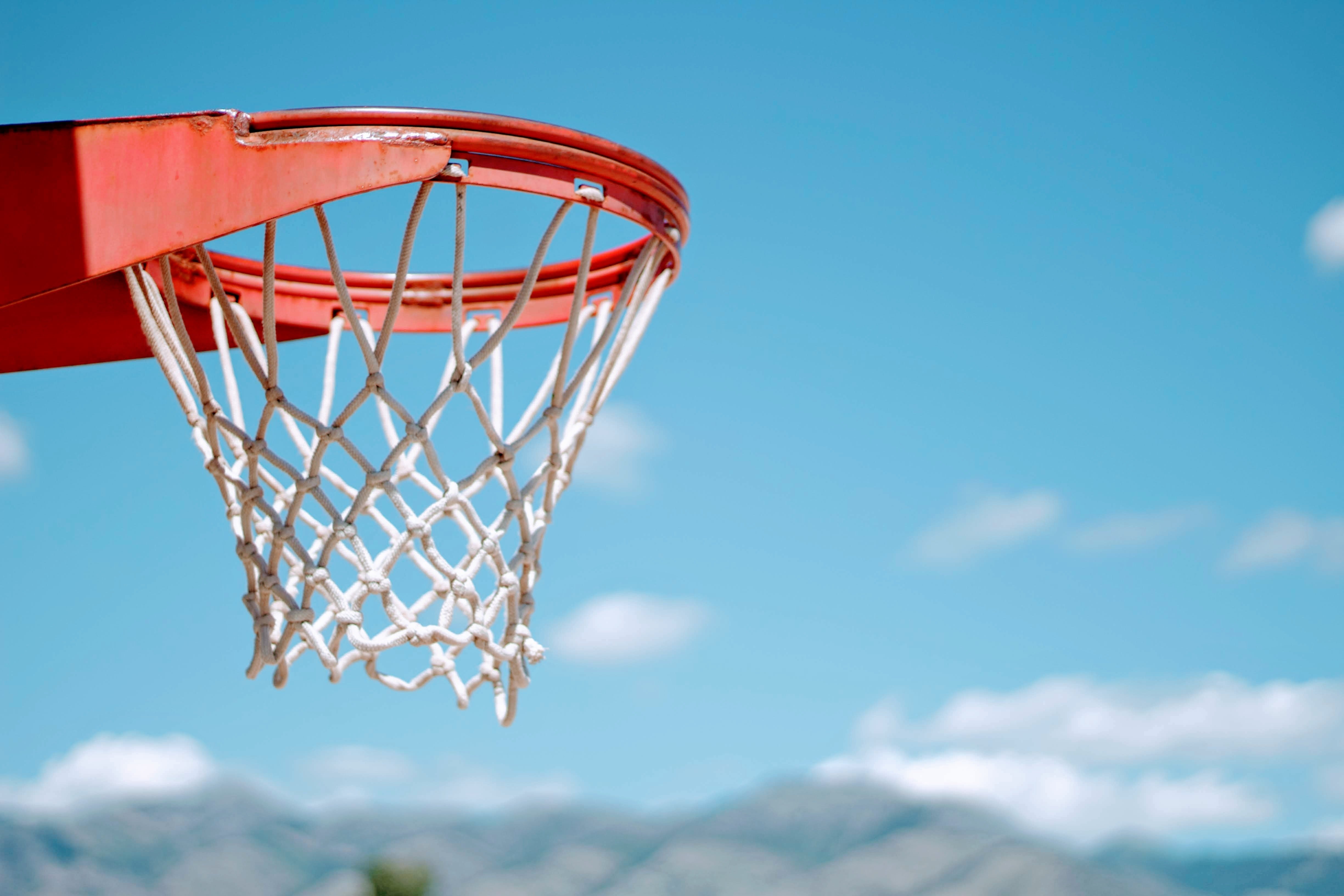 red basketball hoop with white net during daytime