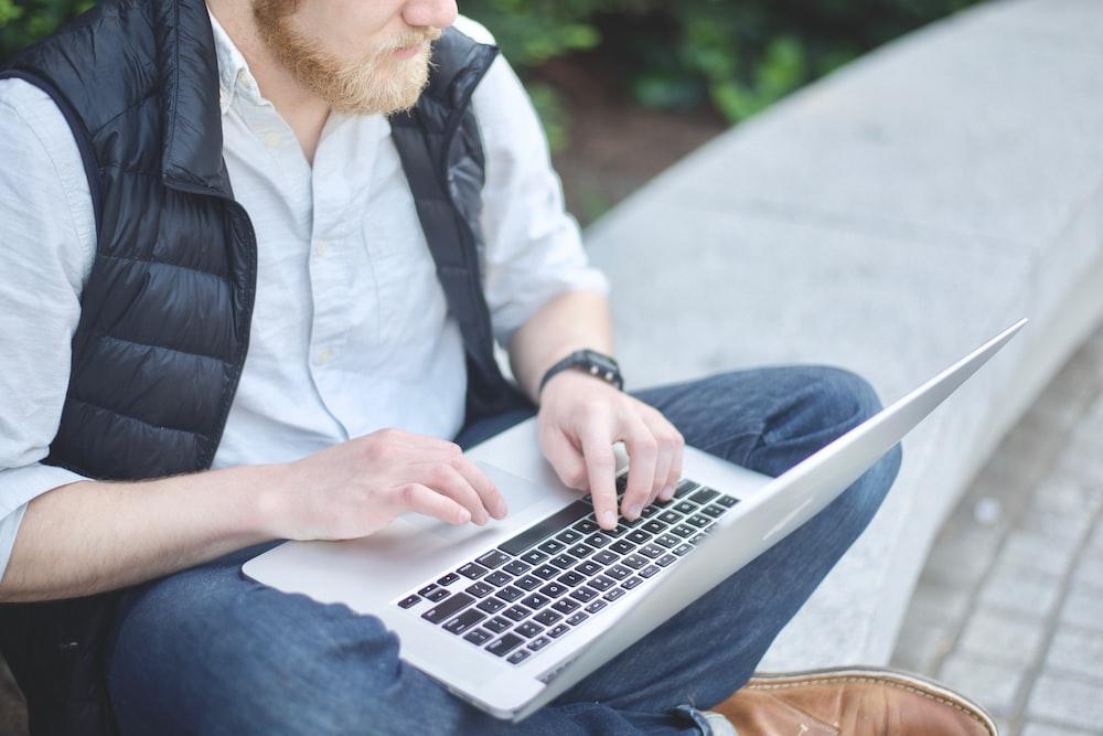 man using MacBook while sitting on bench