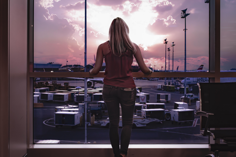 woman standing facing glass window