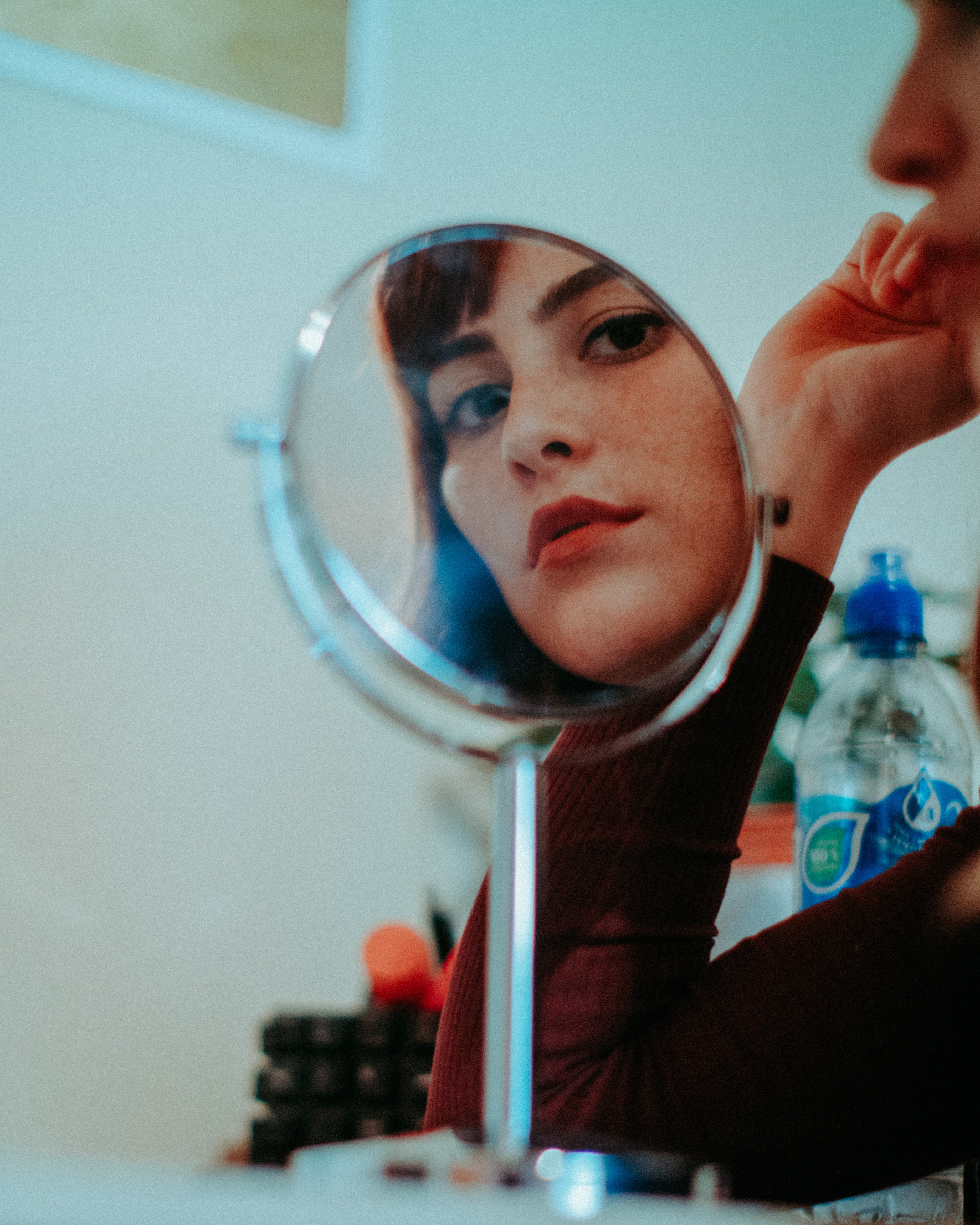 woman staring at round mirror with silver frame