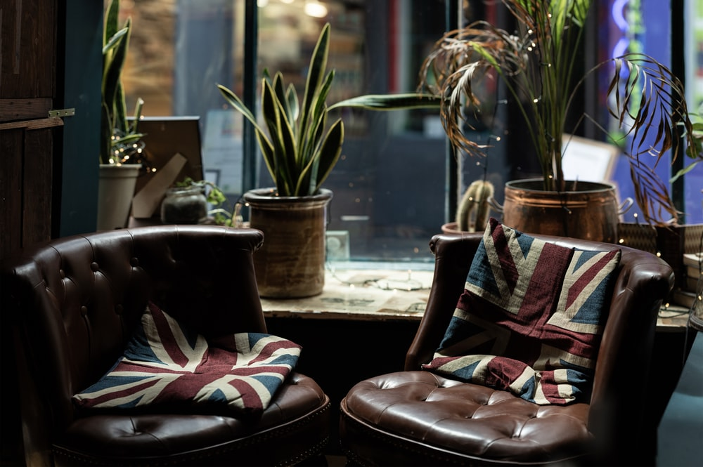 two brown leather couches beside glass window
