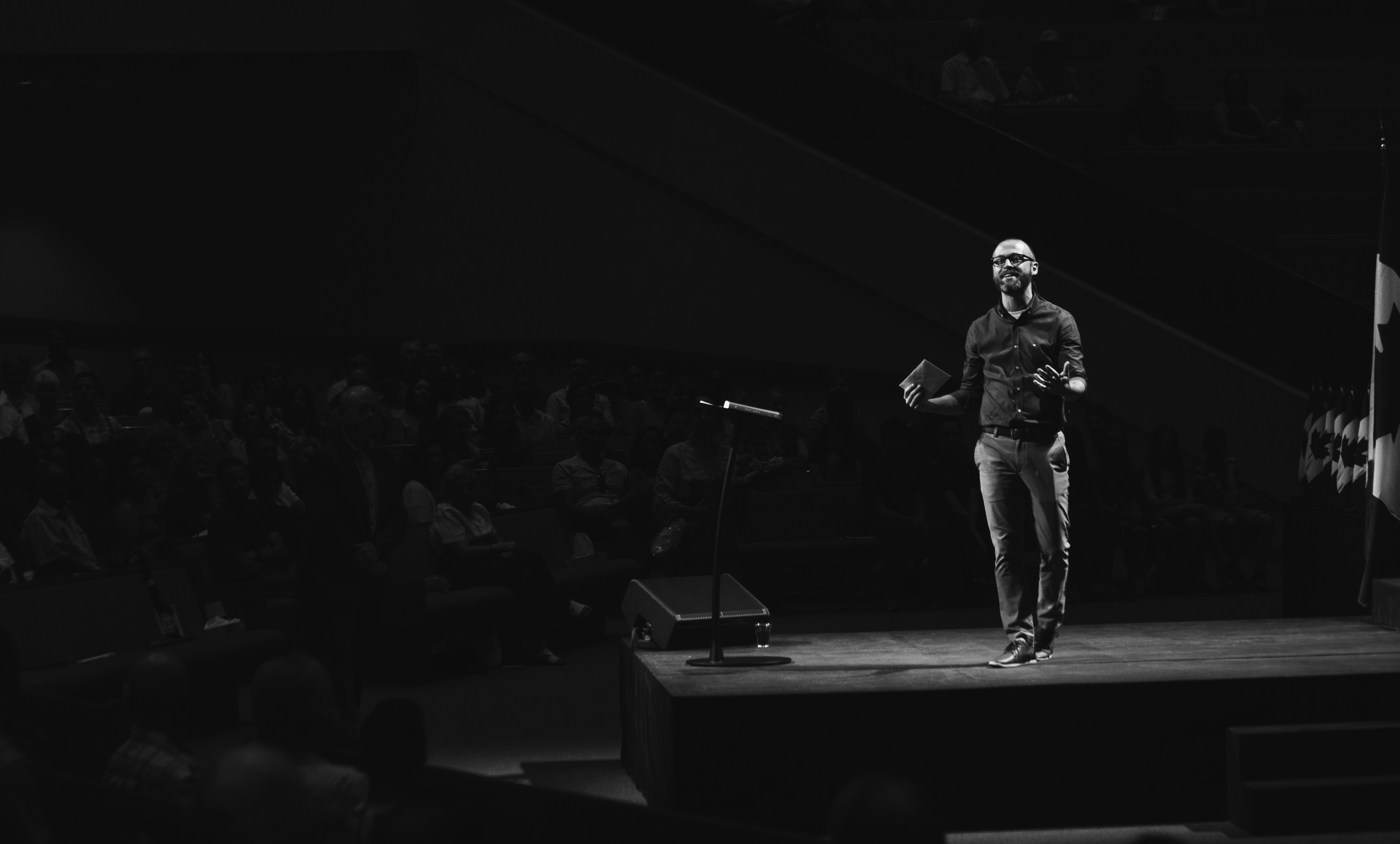 grayscale photo of man walking on platform stage