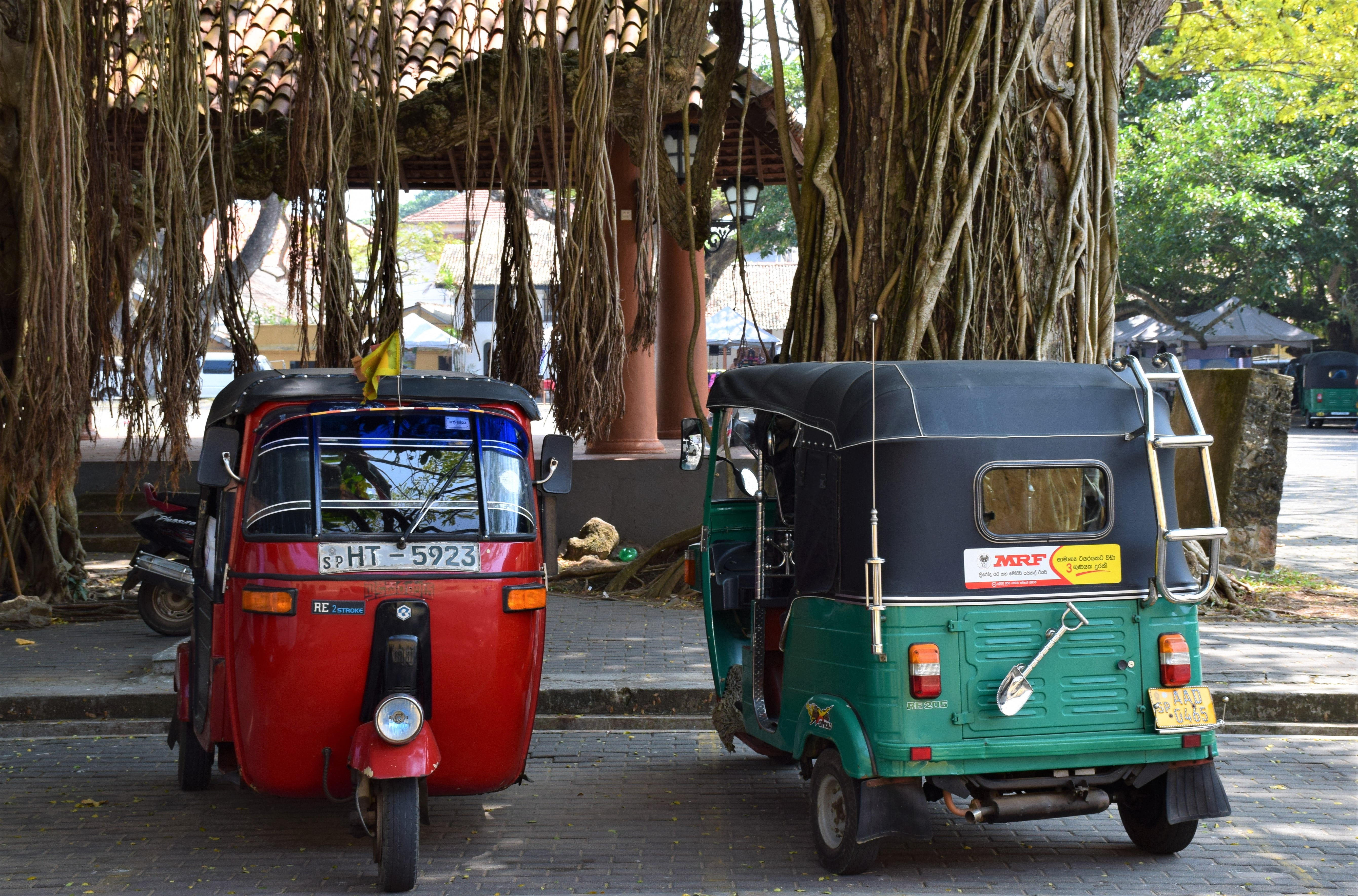 two assorted-color auto rickshaws parked on sidewalk
