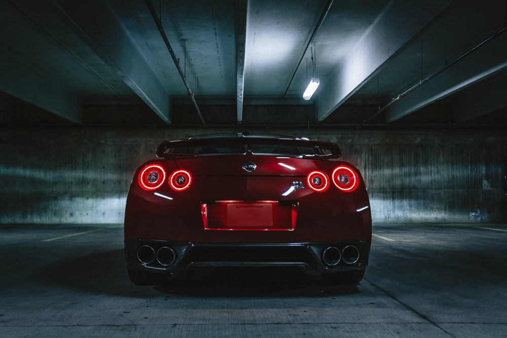 red sports car on concrete flooring