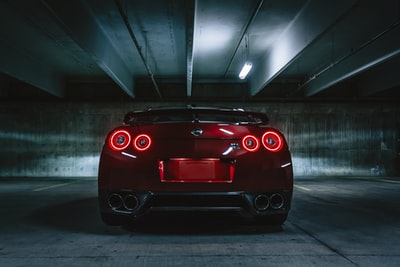 red sports car on concrete flooring nissan teams background