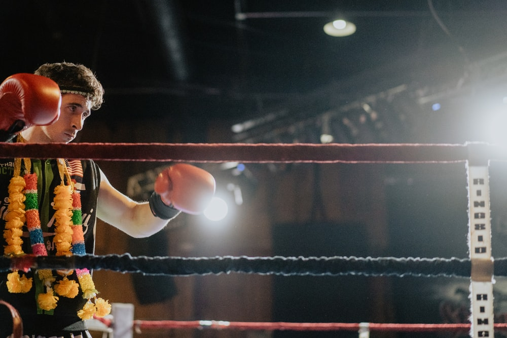 person wearing boxing gloves in ring