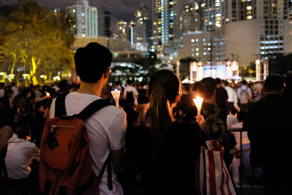 group of people holding candle near buildings