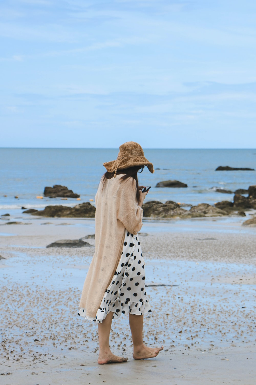 woman wearing sun hat walking along seashore