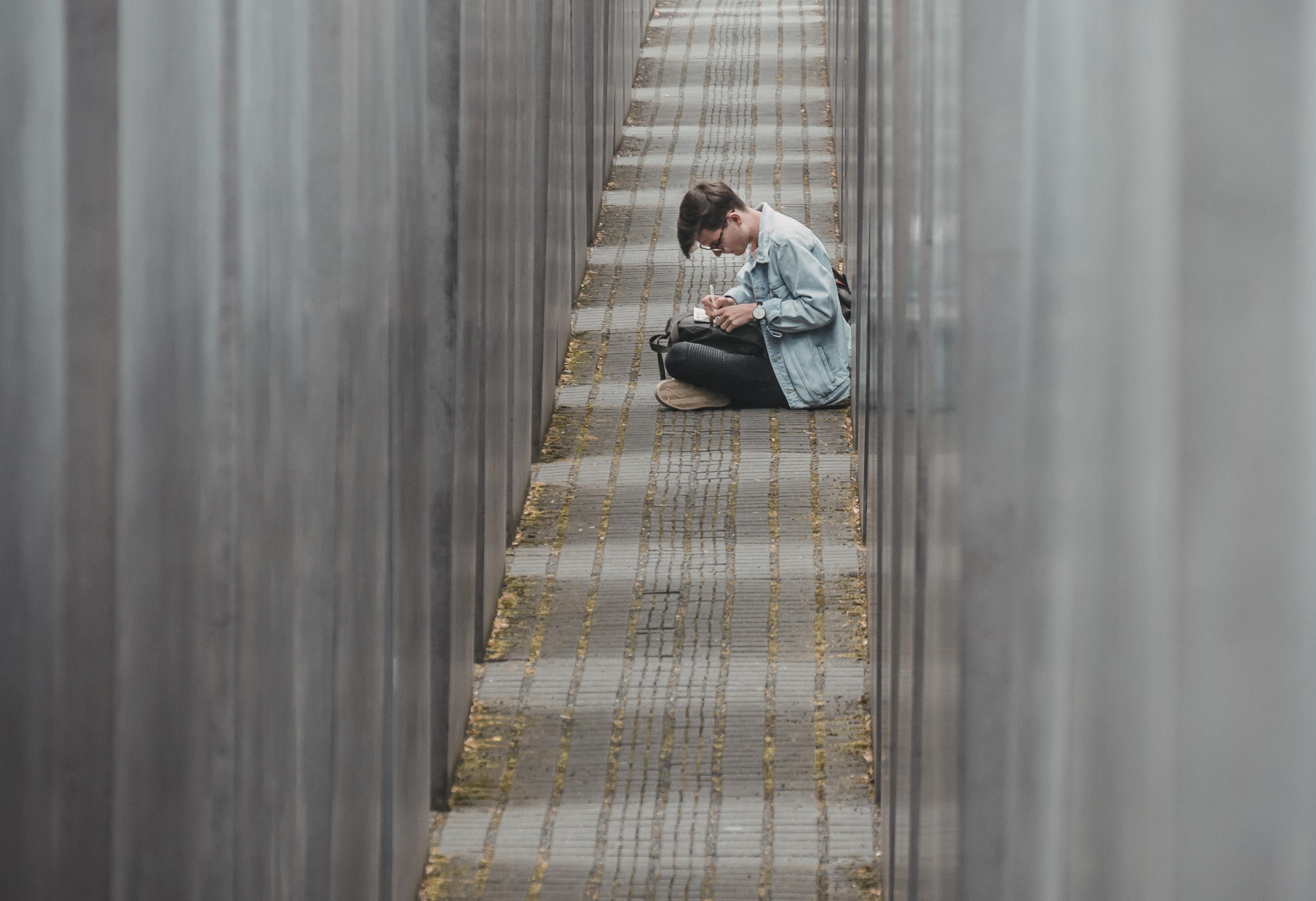 man sitting on pathway writing on paper