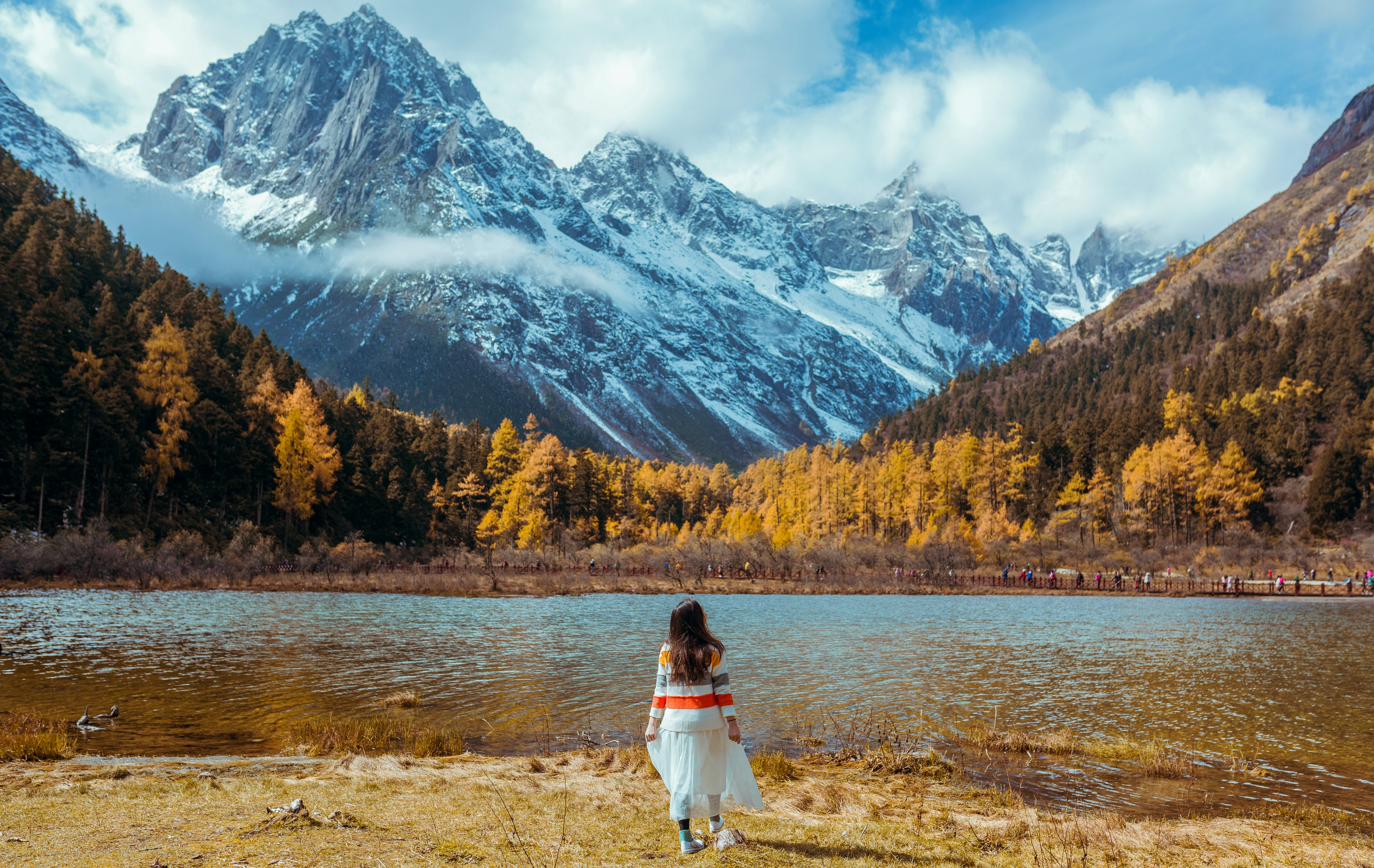 woman standing in front of lake near mountain