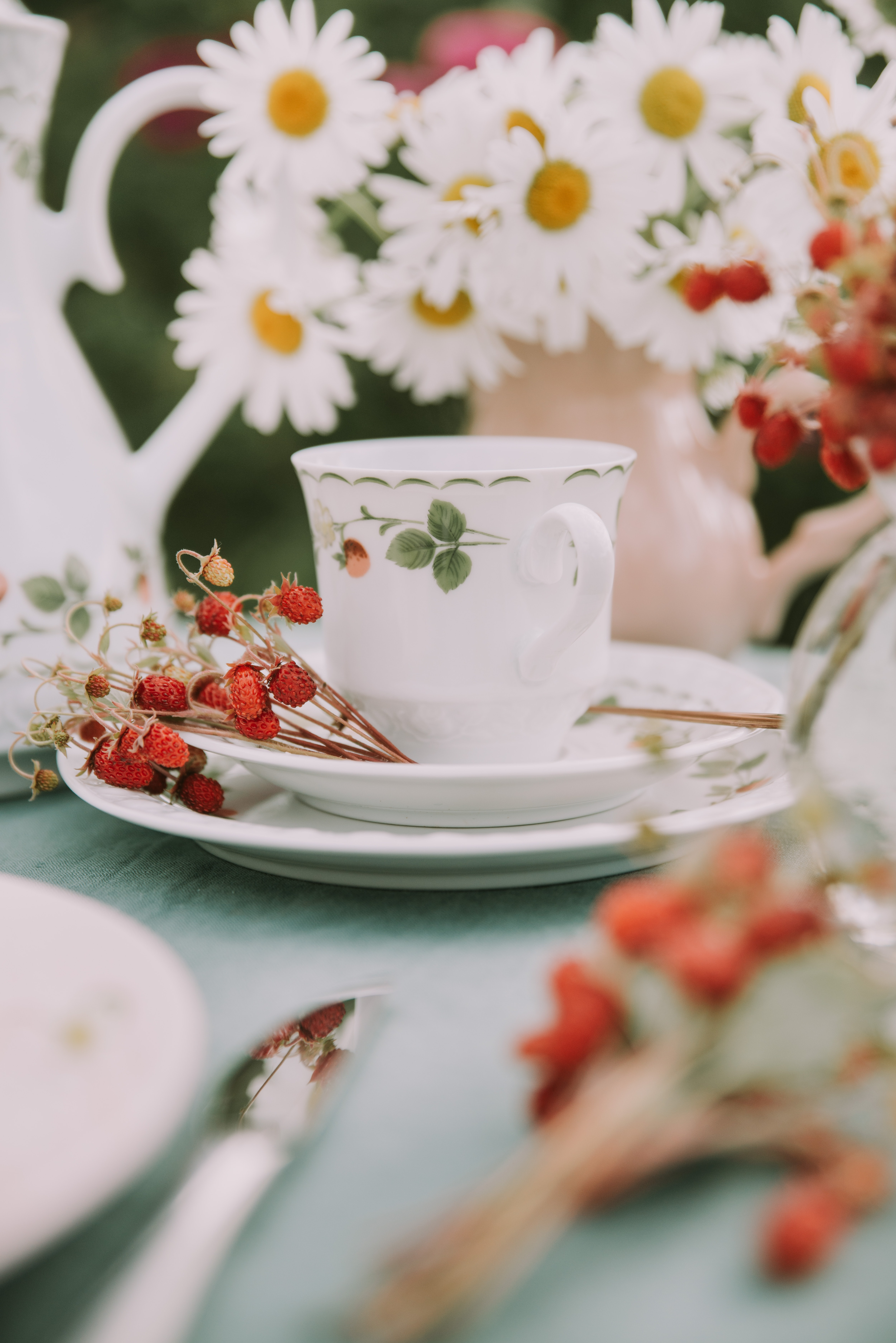 white ceramic teacup and saucer near flowers