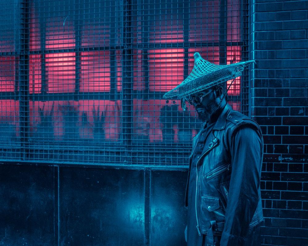 man wearing black vest standing beside window screen outside the building