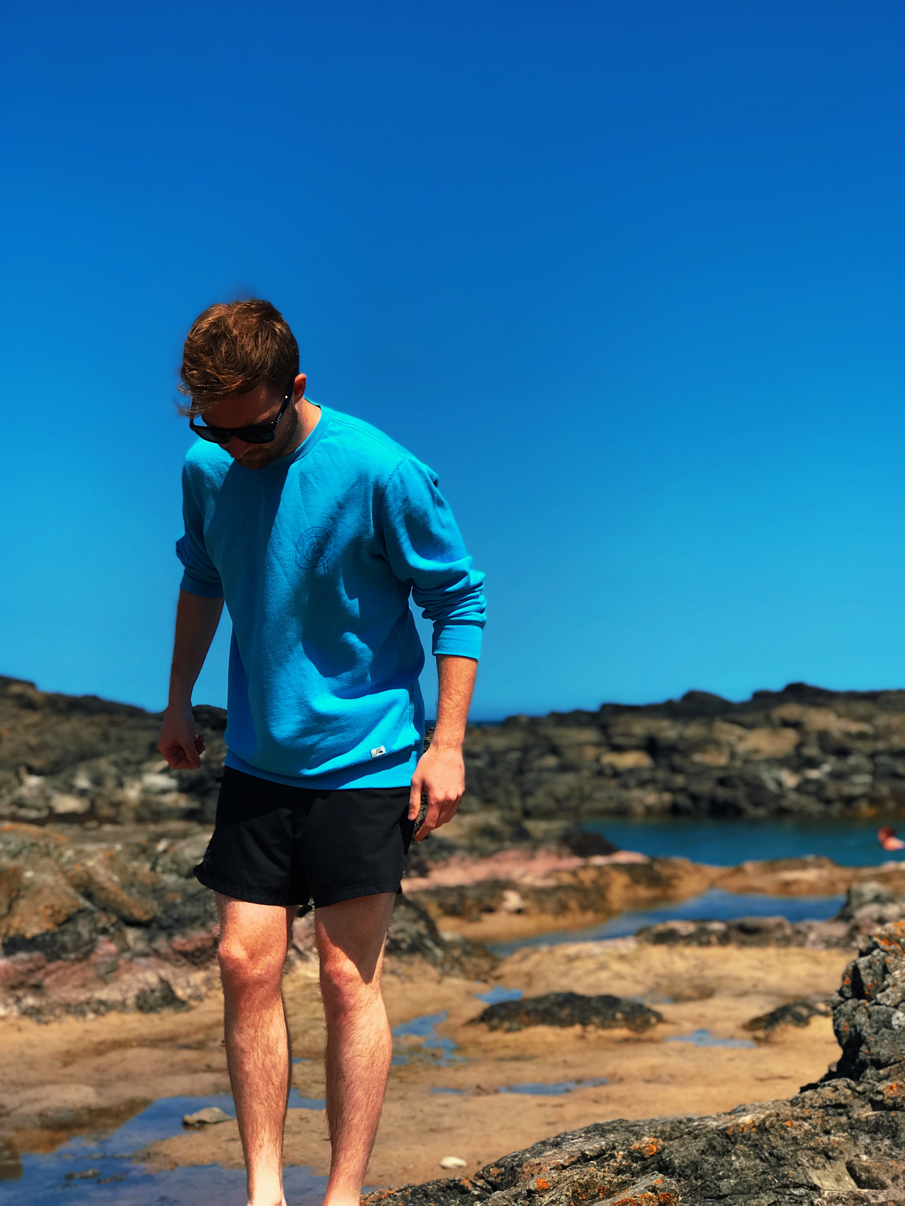 man wearing blue shirt standing on gray rock at daytime