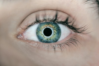 person showing green and black eyelid closeup photography eye zoom background