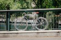 gray bicycle parked on bridge rails