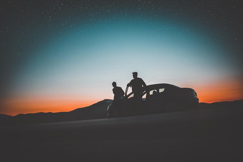 silhouette of two men beside car