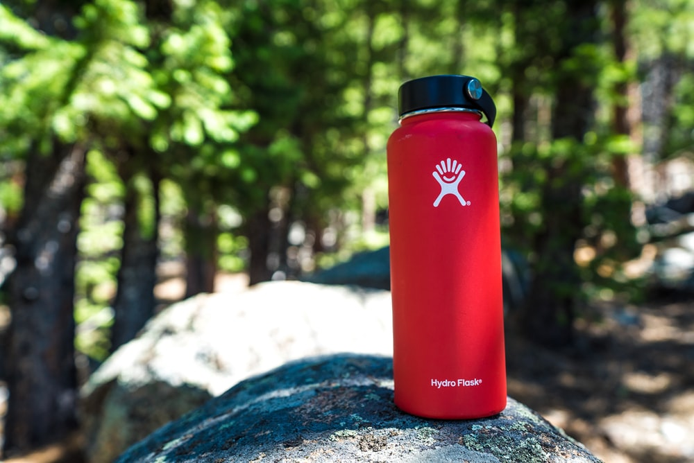 red and black plastic hydro flask on rock