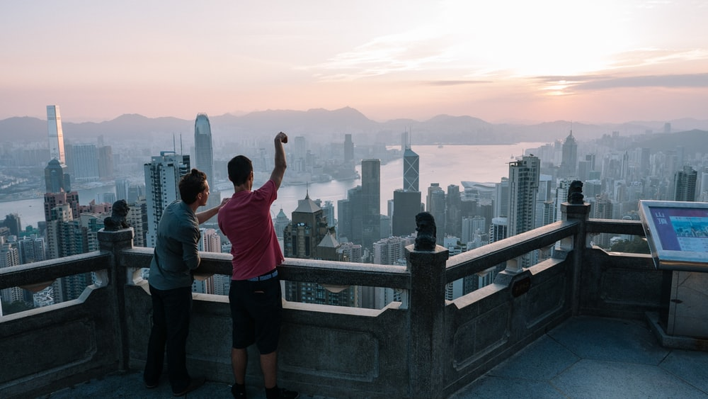 two men standing on top of building pointing to city at daytime