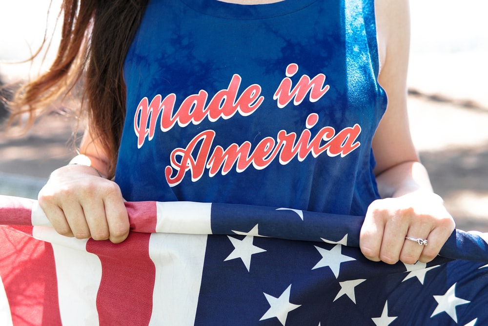 woman in blue sleeveless top holding flag of America