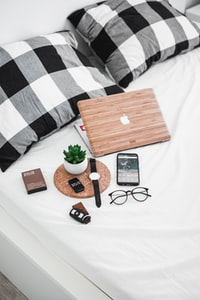 smartphone, eyeglasses, watch, and vehicle fob on bed