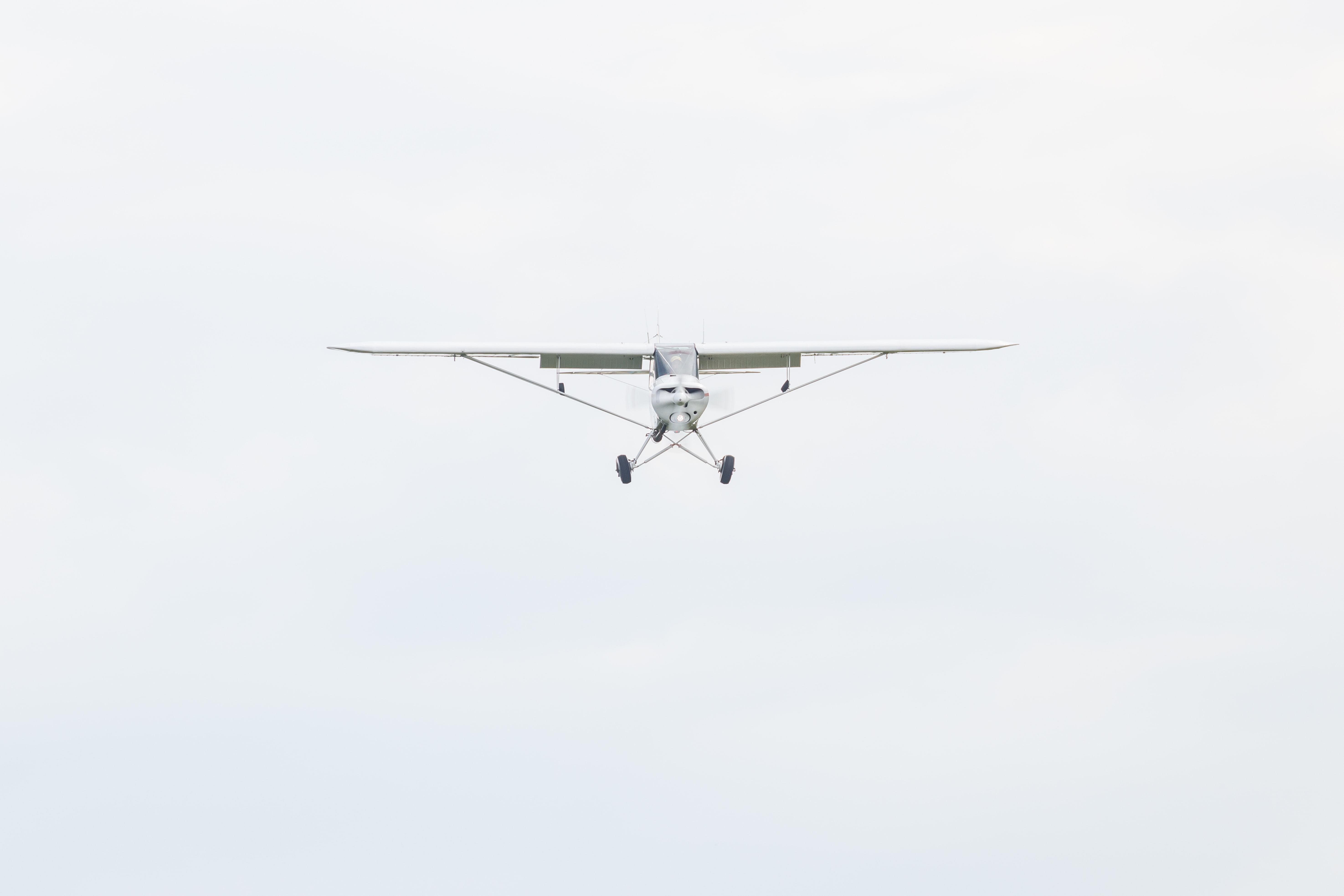 white monoplane flying during daytime