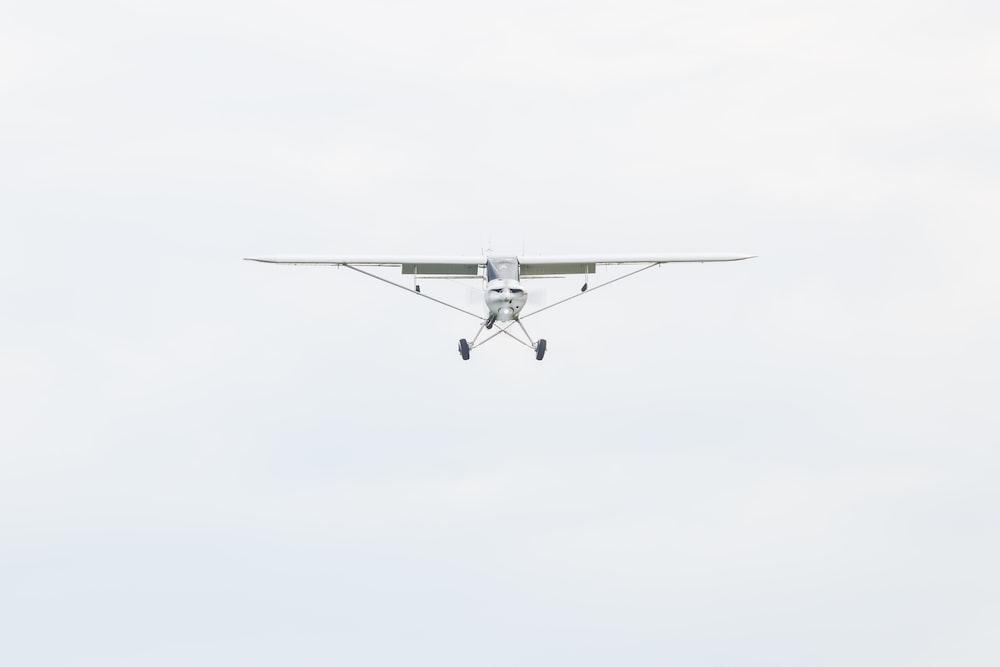 white monoplane flying during daytime
