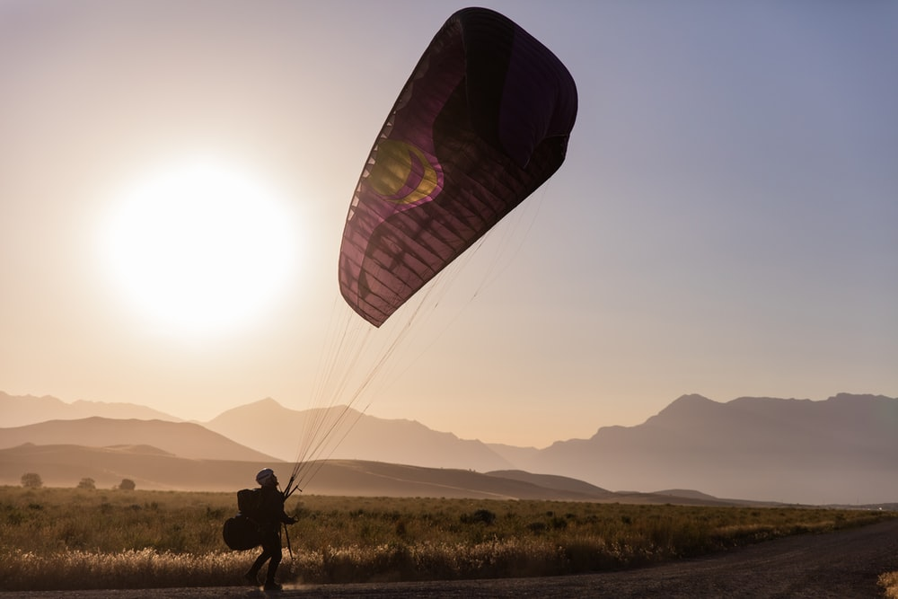 person in black jacket and pants riding on parachute during daytime