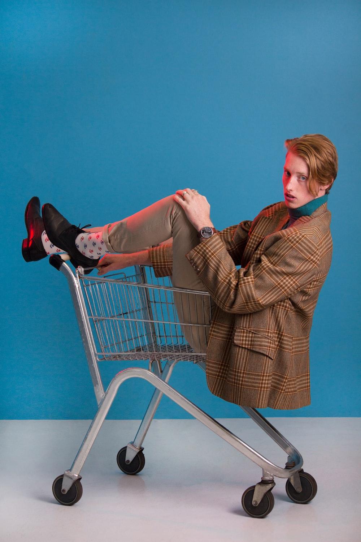 man in brown jacket sitting in shopping cart