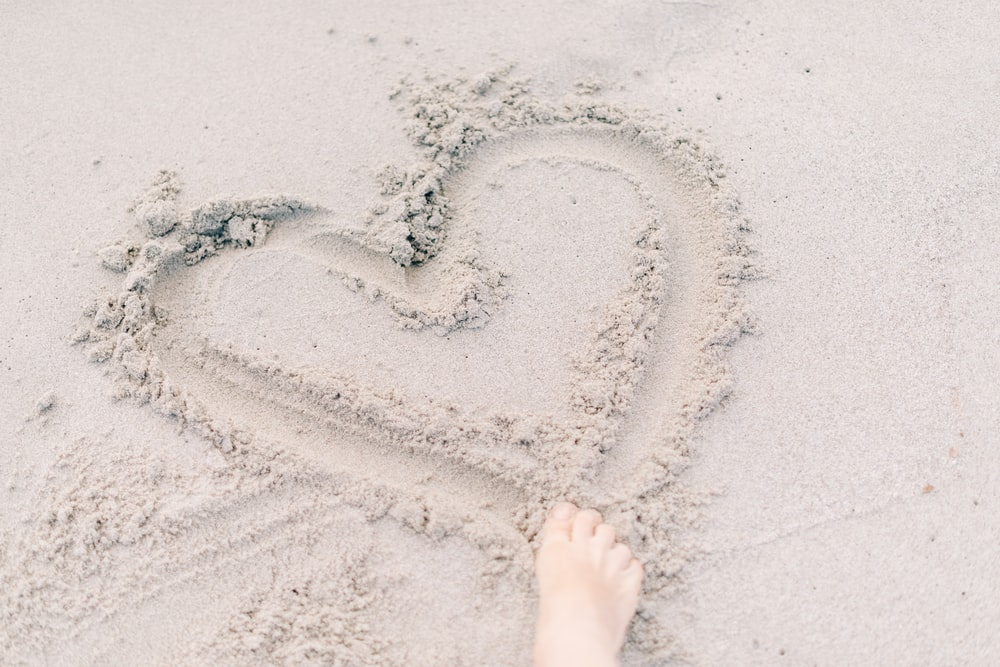 person forming heart on sand using right foot