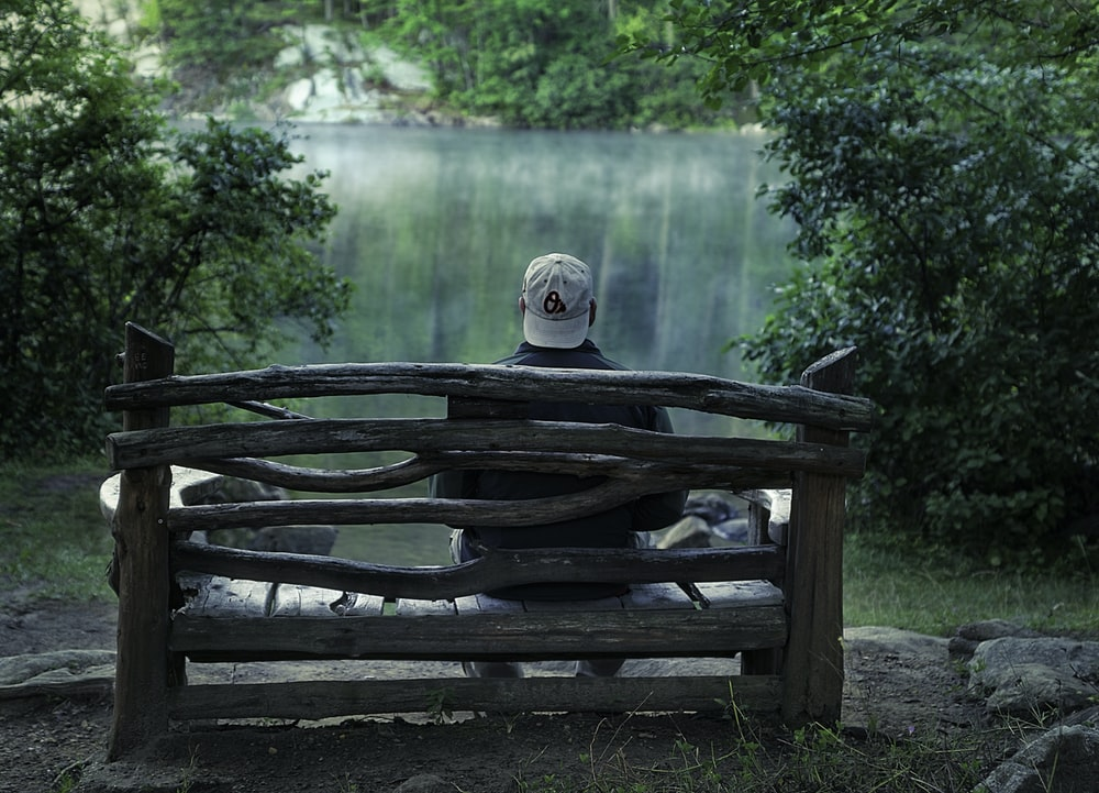 Super Man Sitting On Brown Wooden Bench In Front Of Body Of Water Ocoug Best Dining Table And Chair Ideas Images Ocougorg