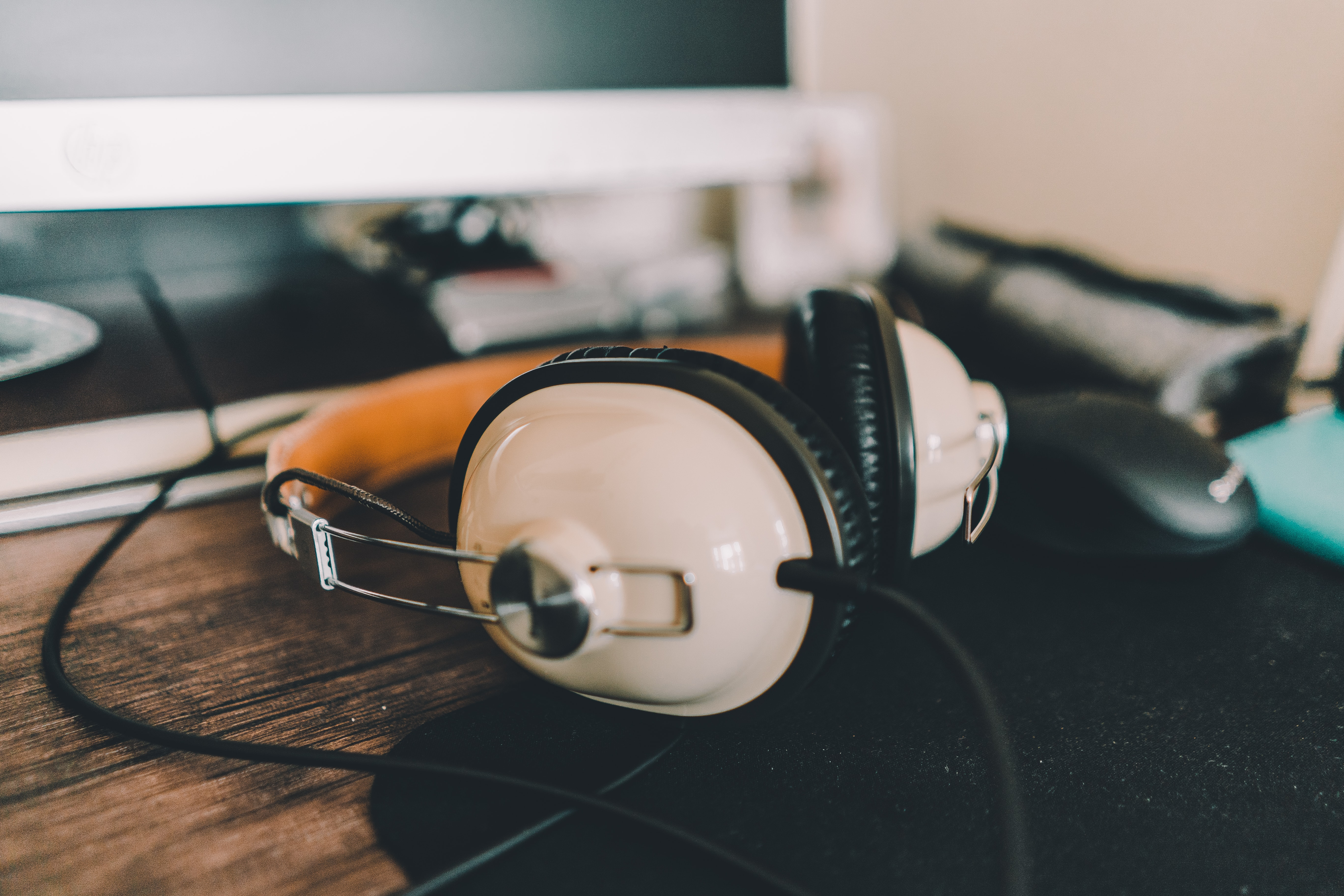 white and black corded headphones on brown wooden shelf