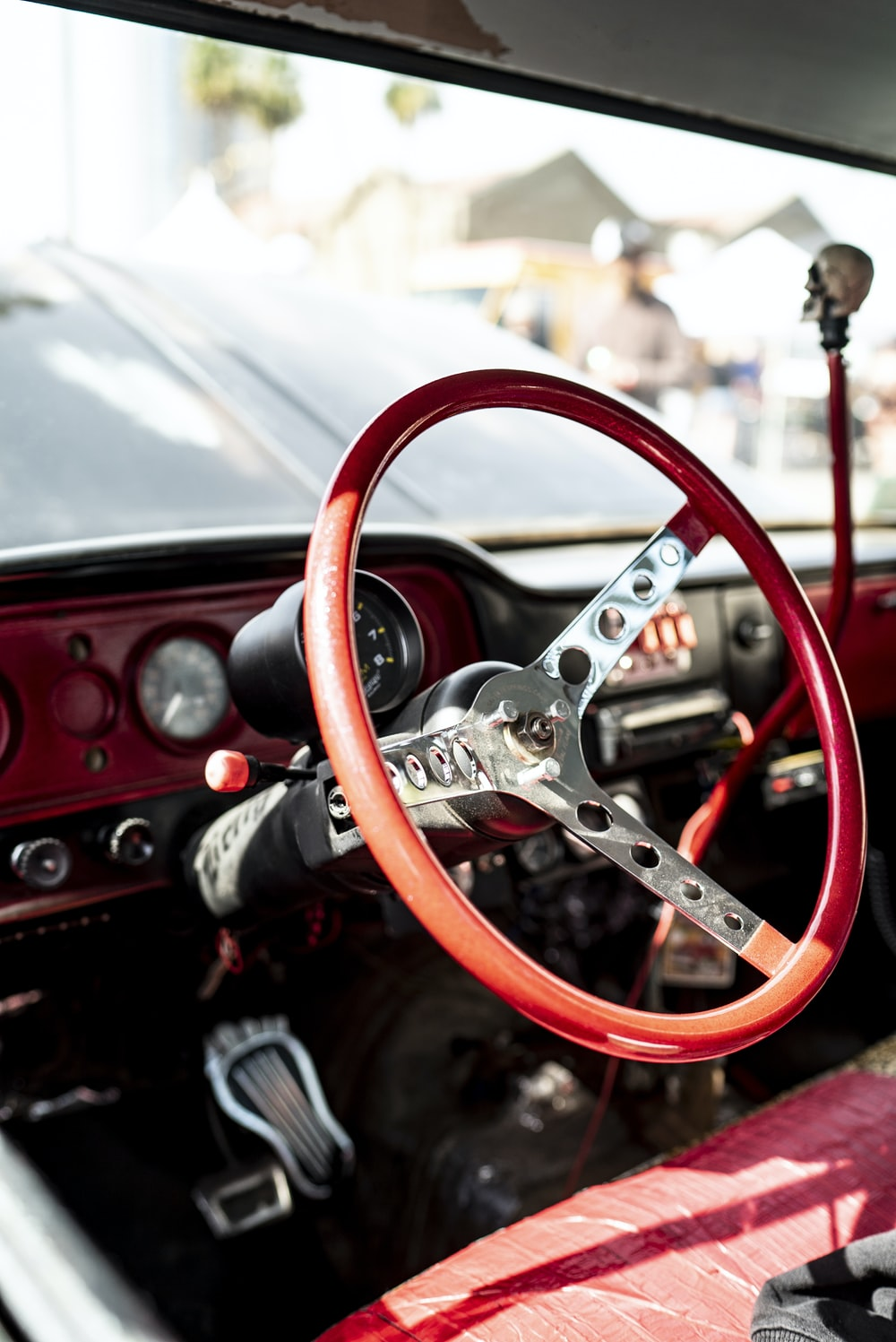 depth of field photography of red vehicle steering wheel