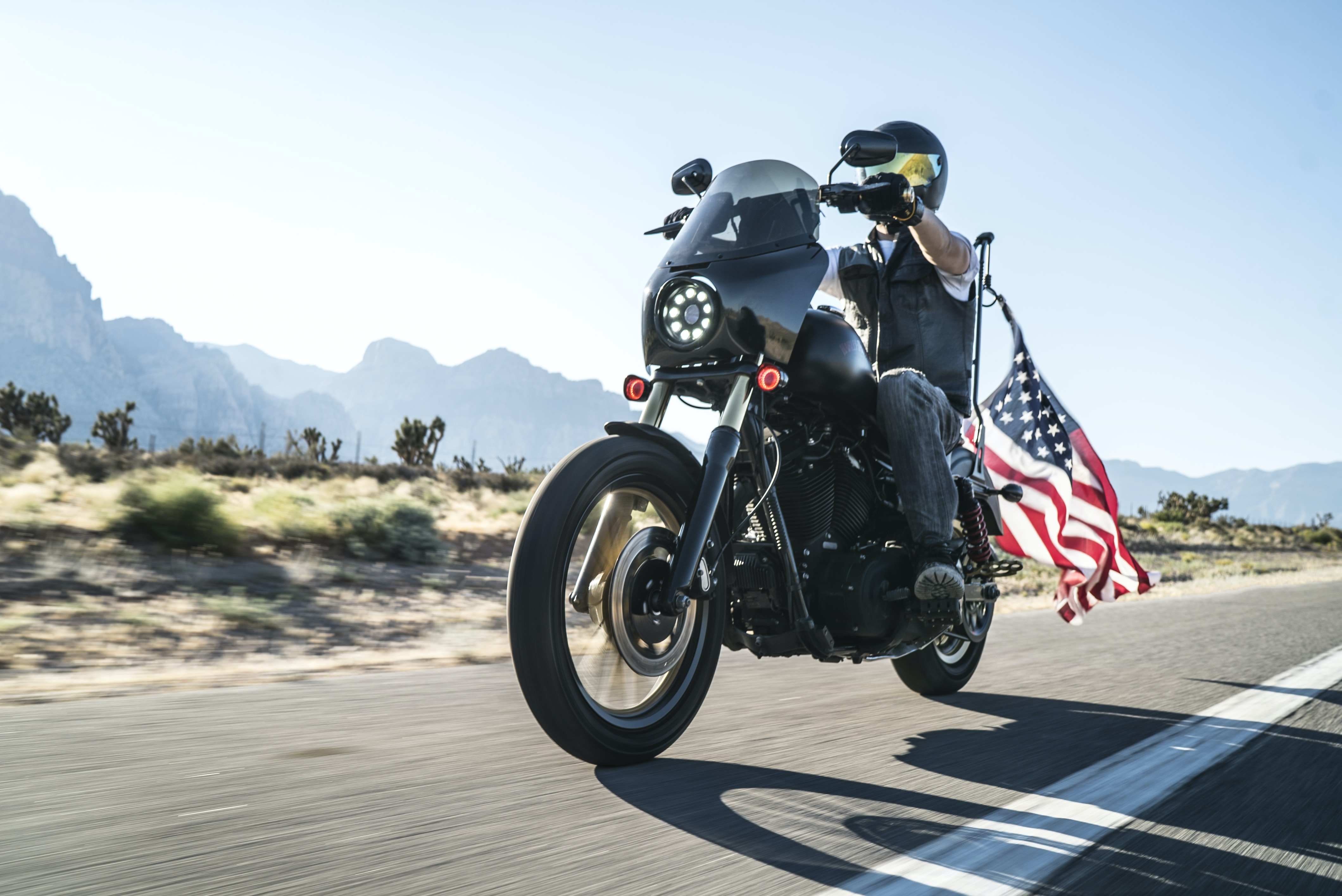 man riding motorcycle with USA flag on back