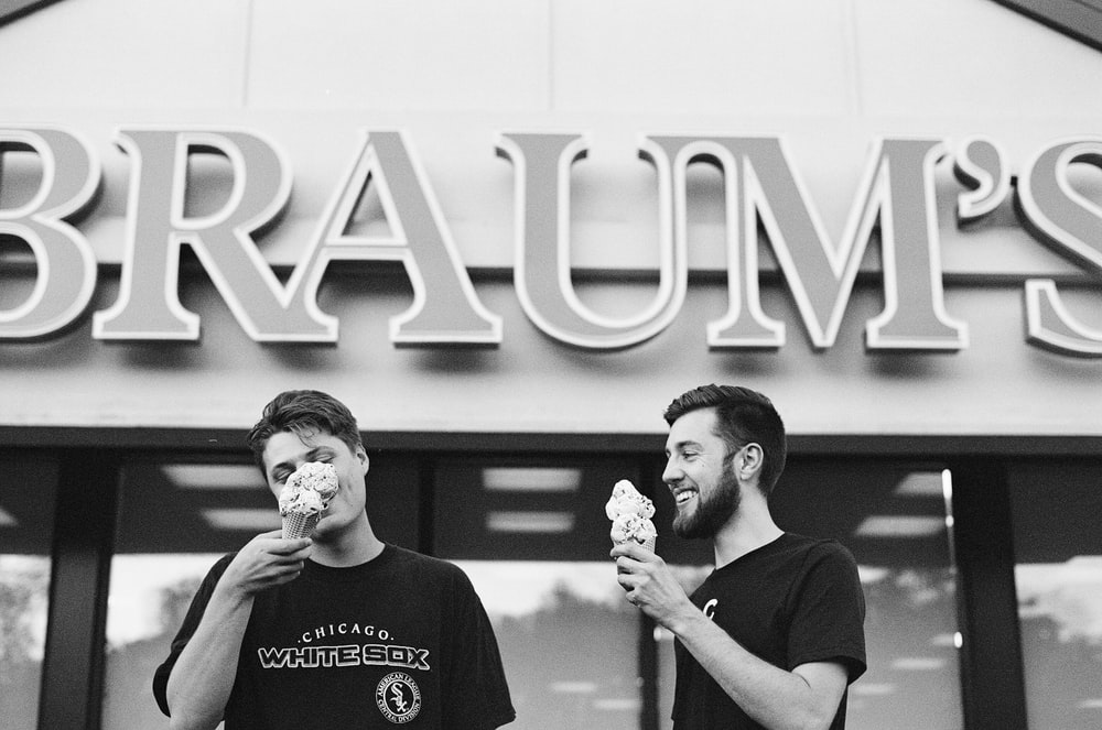 two men eating ice cream grascale photo