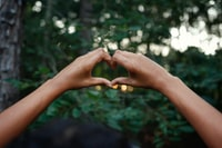 person hands doing heart sign