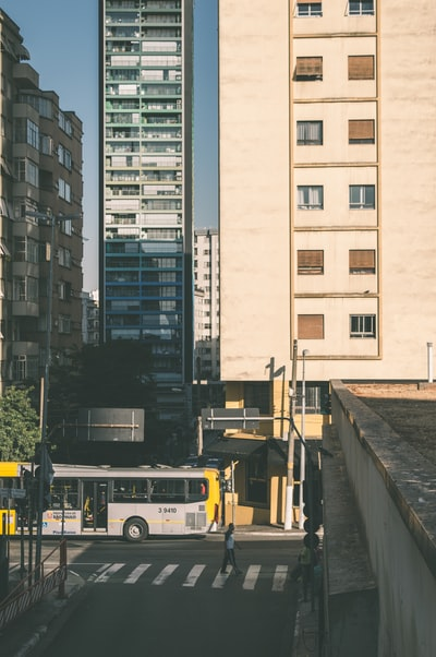 gray bus near beige wall paint high-rise building