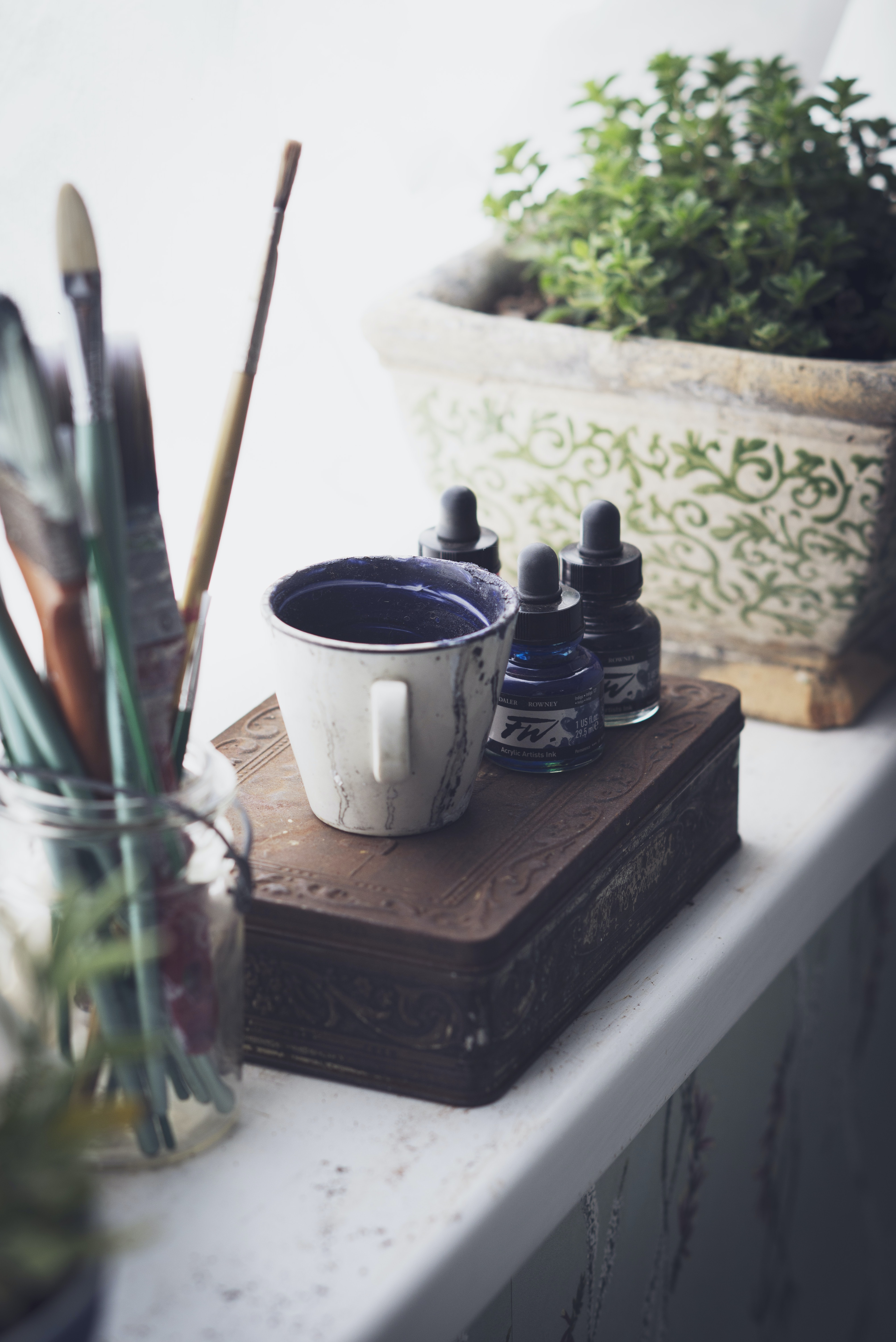 cup and ink bottles on top of chest box