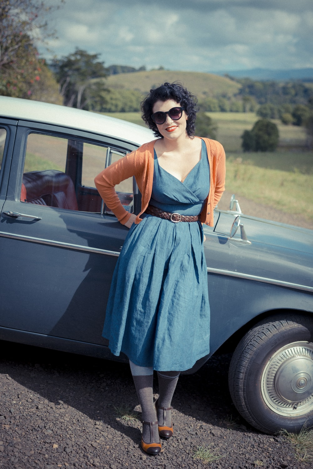 woman leaning on blue car