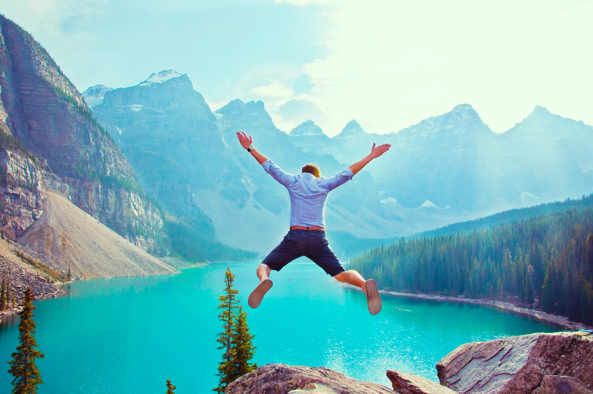 Person jumping off a cliff into a lake with mountains in the background
