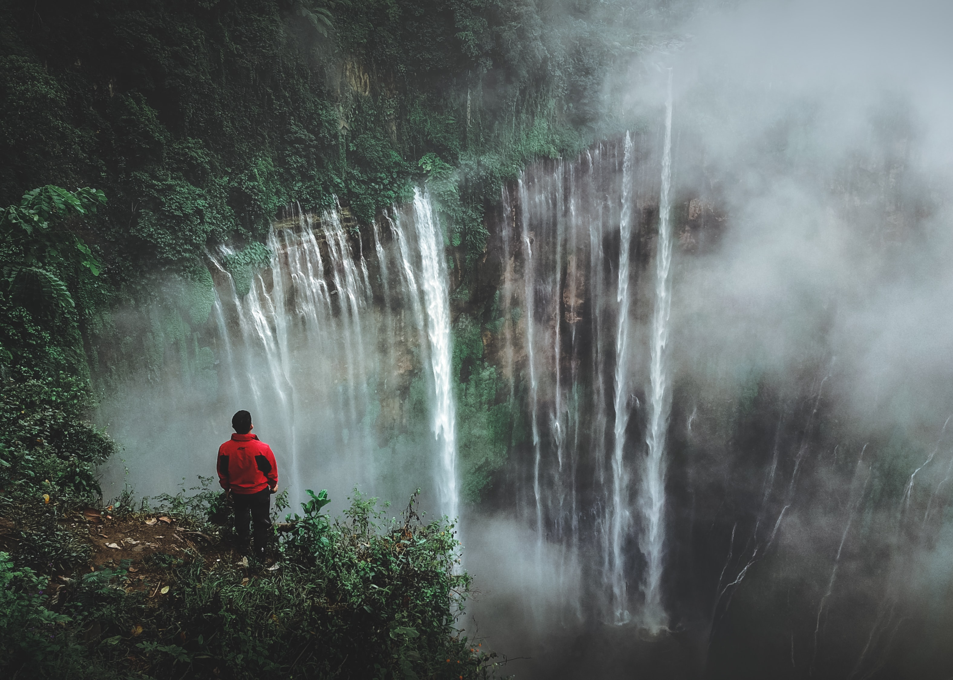 man standing on cliff facing waterfall